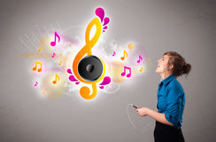 Pretty girl singing and listening to music with musical notes. Getting out of her mouth Royalty Free Stock Photos