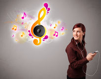 Pretty girl singing and listening to music with musical notes. Getting out of her mouth Royalty Free Stock Photography
