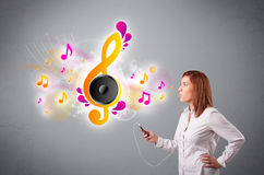 Pretty girl singing and listening to music with musical notes. Getting out of her mouth Stock Photography