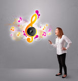 Pretty girl singing and listening to music with musical notes Royalty Free Stock Photography