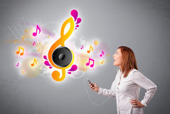 Pretty girl singing and listening to music with musical notes Stock Images