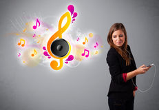 Pretty girl singing and listening to music with musical notes Royalty Free Stock Image