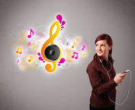 Pretty girl singing and listening to music with musical notes Royalty Free Stock Photos