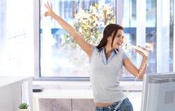 Pretty girl singing in office having fun stock image