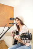 Pretty girl singing and playing guitar Royalty Free Stock Image