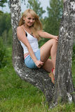 Pretty girl sit on birch. Pretty girl sit on birch in a park Stock Photo