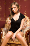 Pretty girl sits on the armchair. Royalty Free Stock Photography