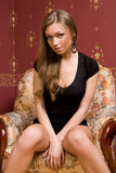 Pretty girl sits on the armchair. Stock Image