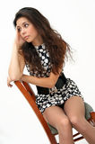 Pretty girl sits on a chair looking thoughtful. Stock Photo