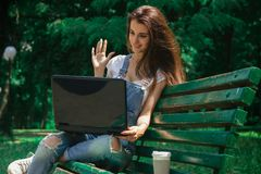 Pretty girl sits and communicates on a laptop Royalty Free Stock Photo