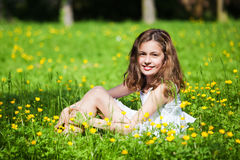 Pretty girl sits in a flower meadow Royalty Free Stock Image