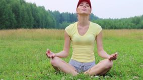 Pretty girl sits on green meadow and meditates at summer evening stock video footage