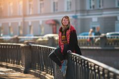 A pretty young girl sits on the railing of the canal embankment in St. Petersburg. stock photos