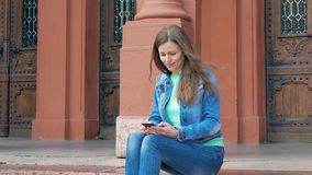 Pretty girl sits on the steps in a cotton jacket and using smartphone. Vintage building in the background. stock video footage