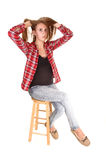 Pretty girl sitting. A tall pretty woman sitting on a chair in jeans and a checkered shirt for white background royalty free stock photography