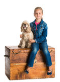 Pretty girl sitting with american spaniel on a wooden chest Royalty Free Stock Image
