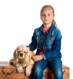 Pretty girl sitting with american spaniel on a wooden chest Royalty Free Stock Photography