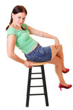 Pretty girl sitting on bar chair. Young, lovely girl in a green top and jeans shorts and red high heels Stock Images
