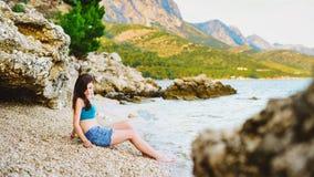 Pretty girl sitting on the beach. In Croatia Stock Photography
