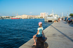 Pretty girl sitting on the beach. Near the sea Stock Image