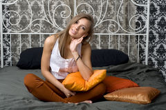 Pretty girl sitting on bed Stock Images