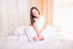 Pretty girl sitting on the bed Stock Photos