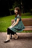 Pretty girl sitting on a bench Stock Photography