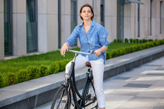 Pretty girl sitting on a bicycle at street Stock Photos