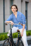 Pretty girl sitting on a bicycle at street Stock Image