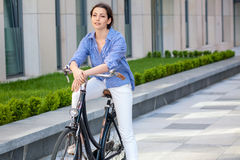 Pretty girl sitting on a bicycle at street Royalty Free Stock Image