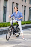 Pretty girl sitting on a bicycle at street Stock Images