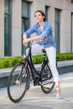 Pretty girl sitting on a bicycle at street Stock Photography