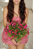 Pretty girl sitting with a bouquet of flowers in pink floral dre Royalty Free Stock Photo