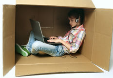 Pretty girl sitting at the box and using laptop. Little girl and laptop in the box stock image