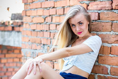 Pretty girl sitting at the brick wall Royalty Free Stock Images