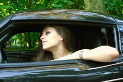 The pretty girl is sitting in the car Stock Photos
