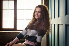 Pretty girl sitting on a chair against the window Royalty Free Stock Photography
