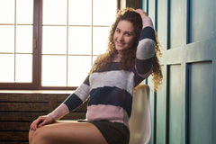 Pretty girl sitting on a chair against the window Stock Images