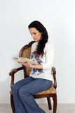 Pretty girl sitting in a chair and reading the book. studio Royalty Free Stock Photography