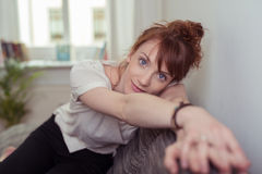 Pretty Girl Sitting on Couch Leaning on her Arms Stock Photo
