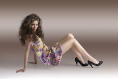 Pretty girl sitting on a floor with body in profile Royalty Free Stock Photography