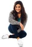 Pretty girl sitting on floor, legs crossed Stock Photography