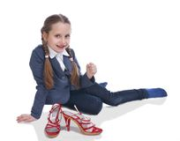 Pretty girl sitting on floor with moms shoes. On a white background Stock Images