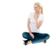 Pretty girl sitting on floor and smiling. Pretty girl in white top and blue jeans sitting on floor, mischievious smile on face Royalty Free Stock Images