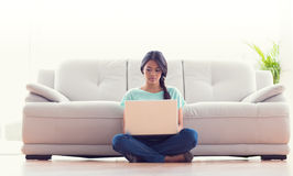 Pretty girl sitting on floor using her laptop Royalty Free Stock Image