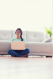 Pretty girl sitting on floor using her laptop smiling at camera Royalty Free Stock Images