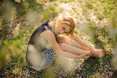 Pretty girl sitting on the grass in park. Pretty blond girl sitting on the grass in park Stock Photos