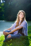 Pretty girl sitting on the grass in sunshine Royalty Free Stock Images
