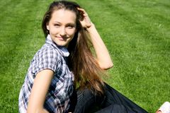 Pretty girl sitting on the green grass Royalty Free Stock Image