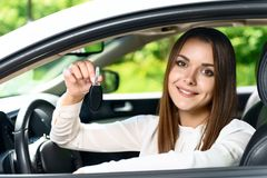 Pretty girl sitting inside car and holding key Royalty Free Stock Photos